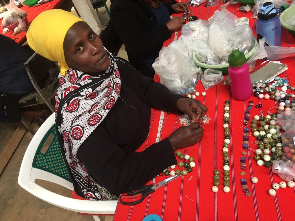 ...then other women assemble the necklaces & bracelets by hand like this...