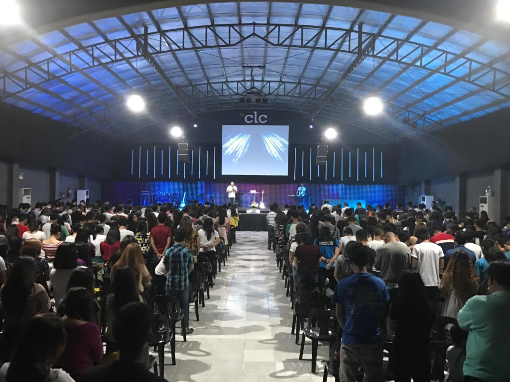 Pastor Joel making the salvation invitation to a packed house at one service